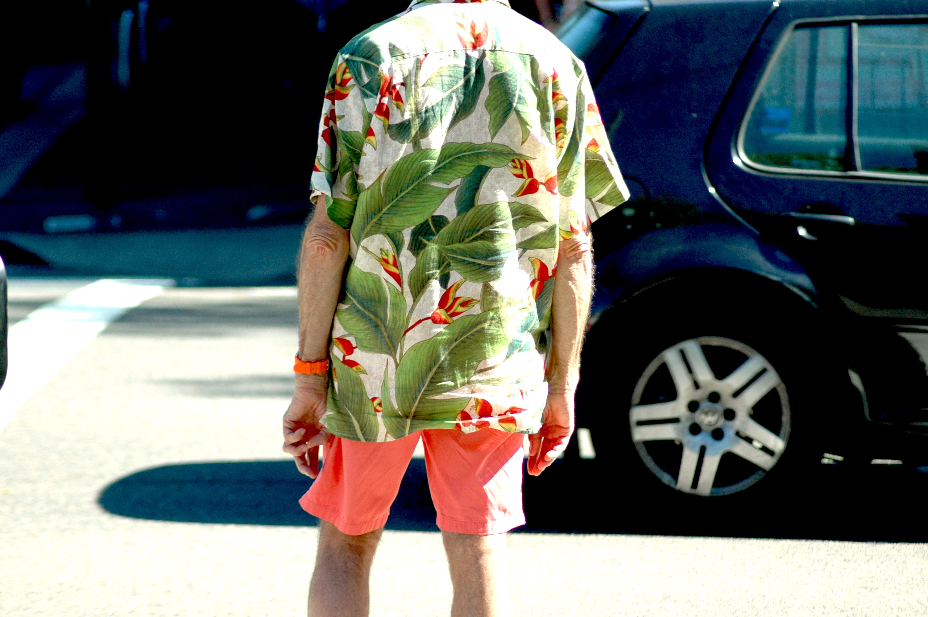 A large floral print Summer shirt, teamed with a neon orange pair of shorts and a matching neon orange watch.